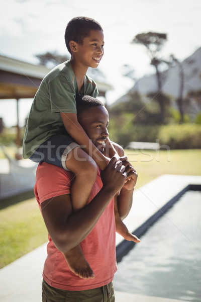 Father carrying son on shoulders near poolside Stock photo © wavebreak_media