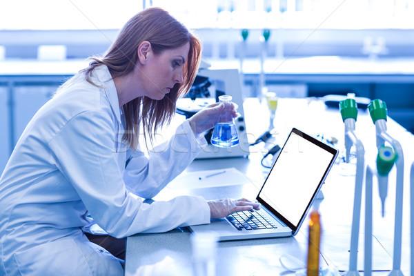 Scientist looking at beaker of chemical Stock photo © wavebreak_media