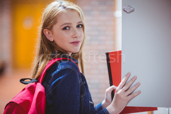 Pretty student with backpack putting notebook in the locker Stock photo © wavebreak_media