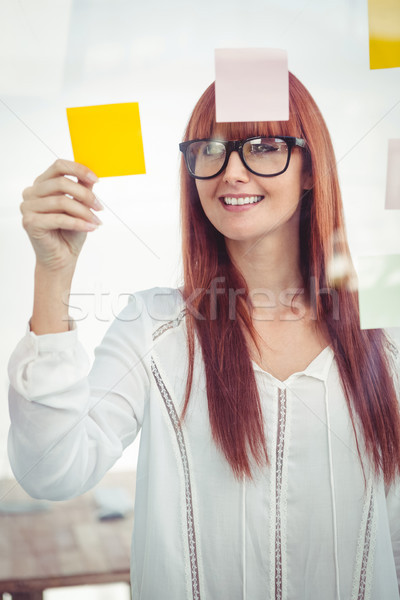 Atraente mulher olhando notas escritório Foto stock © wavebreak_media