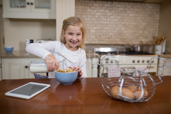Young girl having breakfast in the kitchen at home Stock photo © wavebreak_media