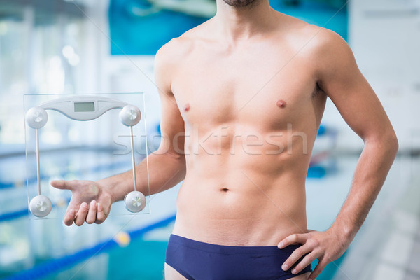 Fit man holding a weighting scale Stock photo © wavebreak_media