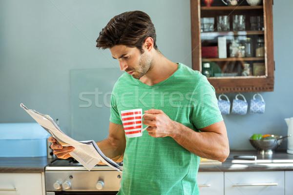 Man reading newspaper while having coffee in kitchen Stock photo © wavebreak_media