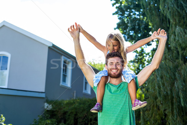 Portrait of father carry daughter on shoulders in yard Stock photo © wavebreak_media