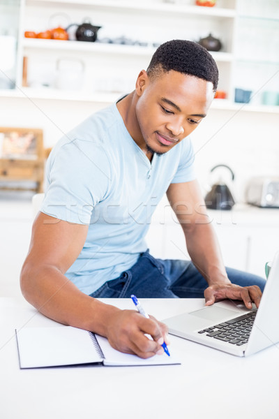 Stock photo: Young man using laptop while writing in diary
