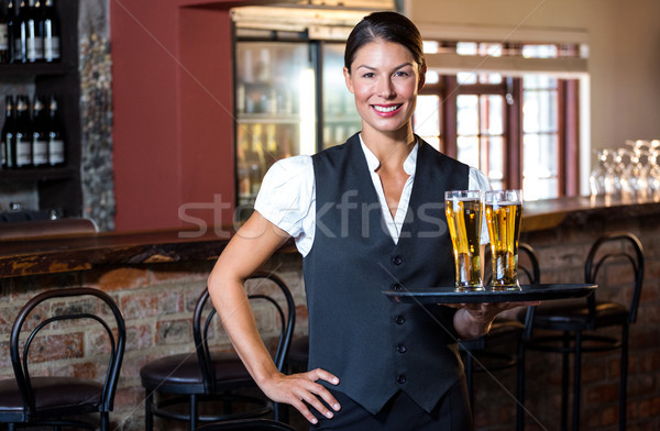 Portrait of waitress holding serving tray with two glass of beer Stock photo © wavebreak_media