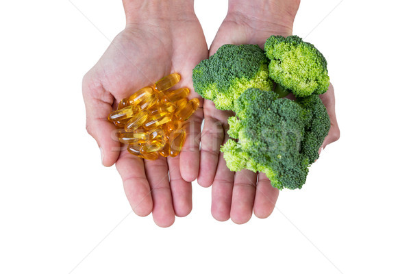 Close-up of hands holding broccoli and vitamin pills Stock photo © wavebreak_media