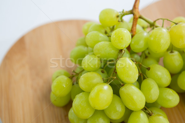 Close-up of green bunch of grapes on chopping board Stock photo © wavebreak_media