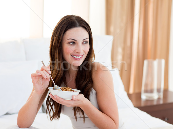 Pretty woman eating cereals sitting on bed Stock photo © wavebreak_media