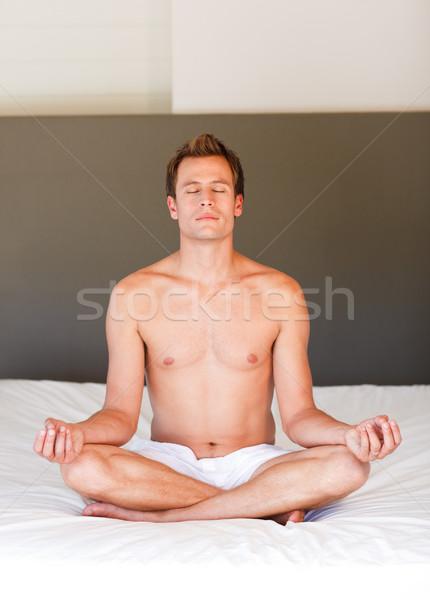 Jóképű férfi meditáció ágy jóképű fiatalember mosoly Stock fotó © wavebreak_media