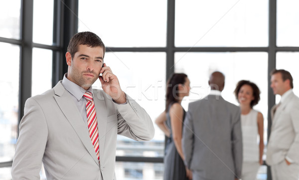 Self-assured businessman holding a phone at workplace with his colleagues Stock photo © wavebreak_media