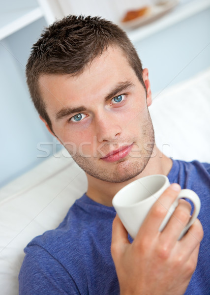 Portrait of a serious young man looking at the camera holding a cup in the living-room Stock photo © wavebreak_media