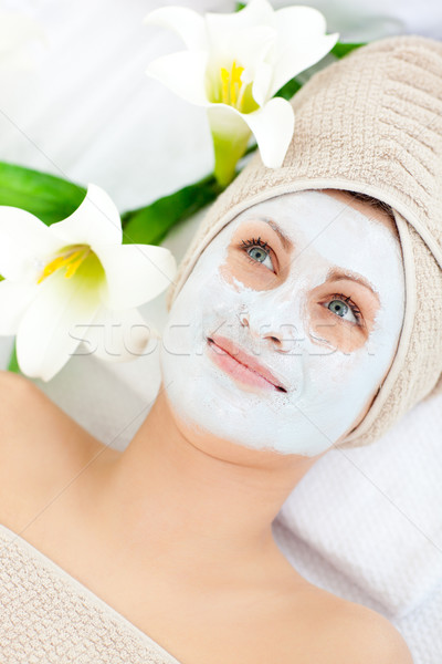 Beautiful woman with cream on her face in a spa lying on a massage table Stock photo © wavebreak_media