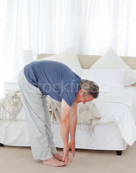 Mature man stretching in his bedroom Stock photo © wavebreak_media