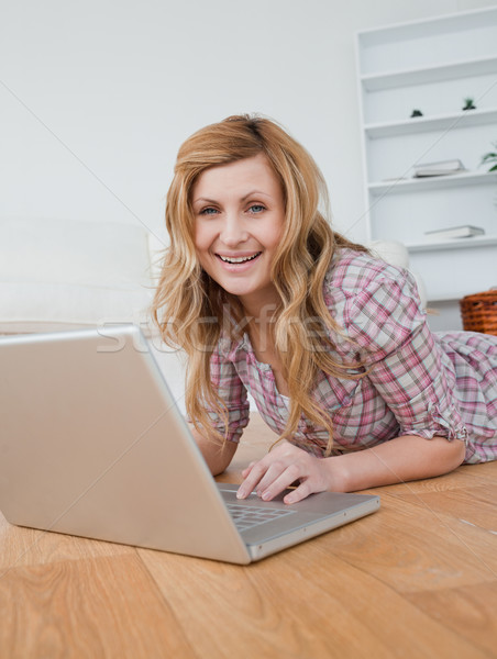 Blonde woman chatting on her laptop lying down on the floor Stock photo © wavebreak_media