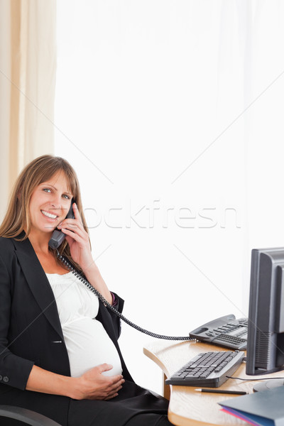 Good looking pregnant woman on the phone while working at the office Stock photo © wavebreak_media