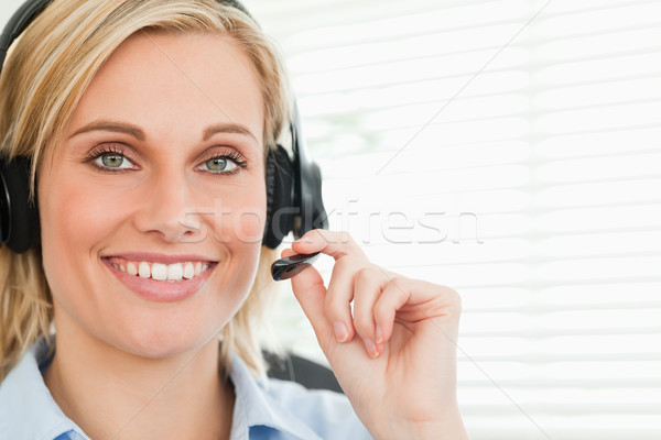 Close up of a smiling businesswoman with headset looking into camera in her office Stock photo © wavebreak_media
