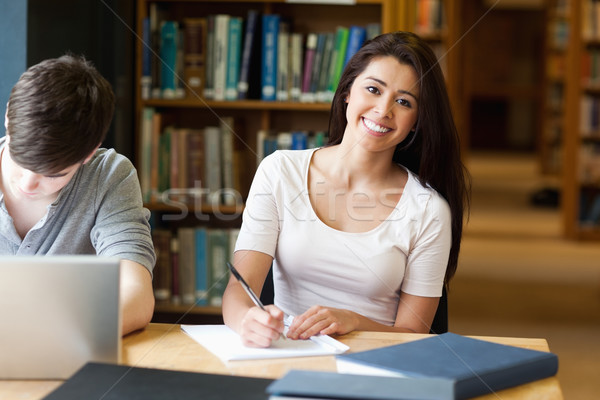 Smiling student writing a paper in the library Stock photo © wavebreak_media