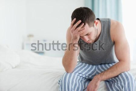 Doente homem sessão cama cabeça mão Foto stock © wavebreak_media