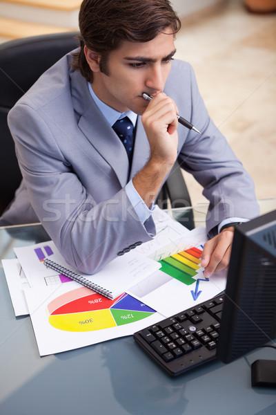 Young businessman working on statistics at his desk Stock photo © wavebreak_media
