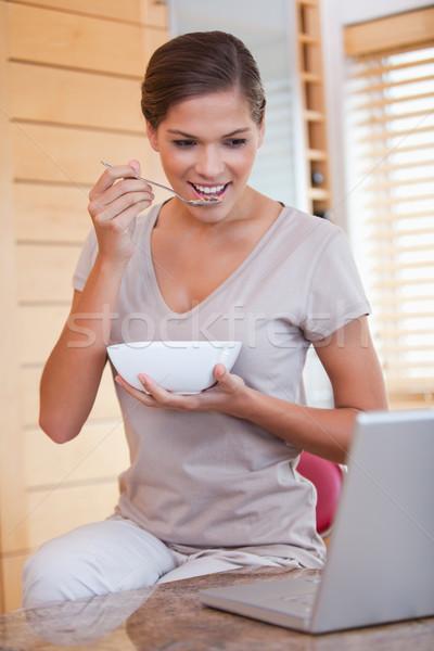 Jeune femme manger céréales portable heureux maison Photo stock © wavebreak_media