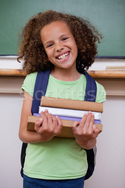 Portrait of a smiling schoolgirl holding her books in a classroom Stock photo © wavebreak_media