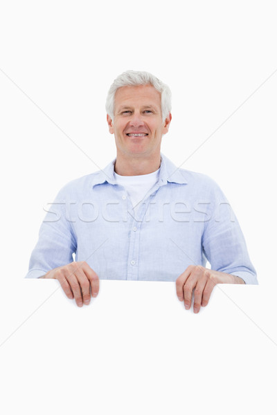 Portrait of a mature man standing behind blank panel against a white background Stock photo © wavebreak_media