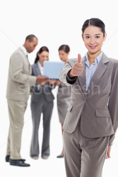 Businesswoman smiling and approving with co-workers watching a laptop in the background Stock photo © wavebreak_media