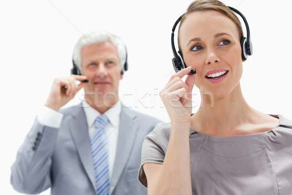 Close-up of a woman talking and wearing a headset with a white hair businessman in the background Stock photo © wavebreak_media