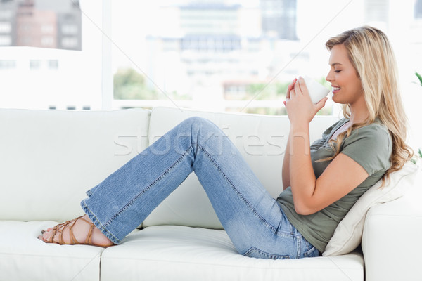 A woman is sitting across the couch as she holds a cup of coffee up to her nose, eyes closed and smi Stock photo © wavebreak_media
