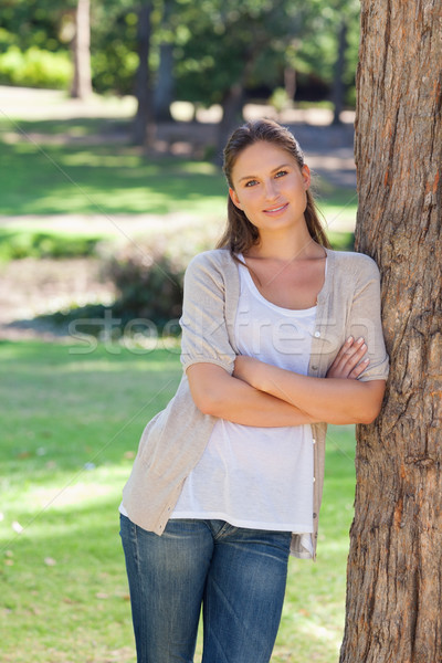 Smiling woman with her arms folded leaning against a tree Stock photo © wavebreak_media