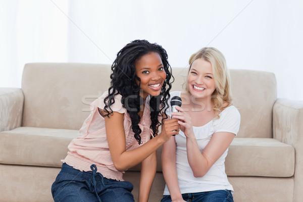 Dois mulheres jovens sessão piso microfone Foto stock © wavebreak_media