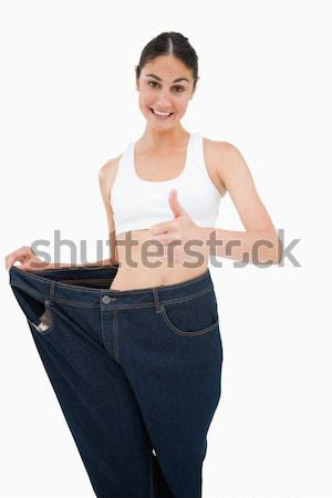 Happy brunette lost a lot of weight against white background Stock photo © wavebreak_media