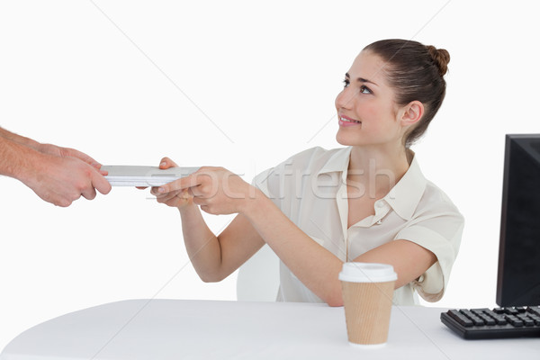 Stock photo: Businesswoman receiving documents against a white background