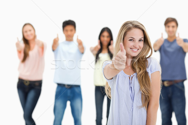 Close-up of people smiling and approving with one woman in foreground against white background Stock photo © wavebreak_media