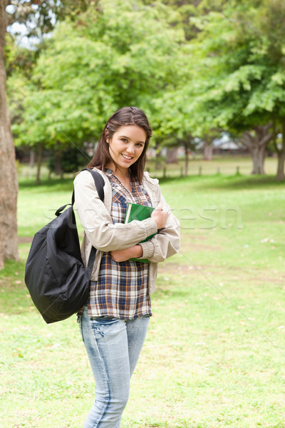 Stock photo: Young student holding textbook while posing in a park