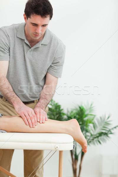 Brunette masseur massaging the leg of a woman in a room Stock photo © wavebreak_media