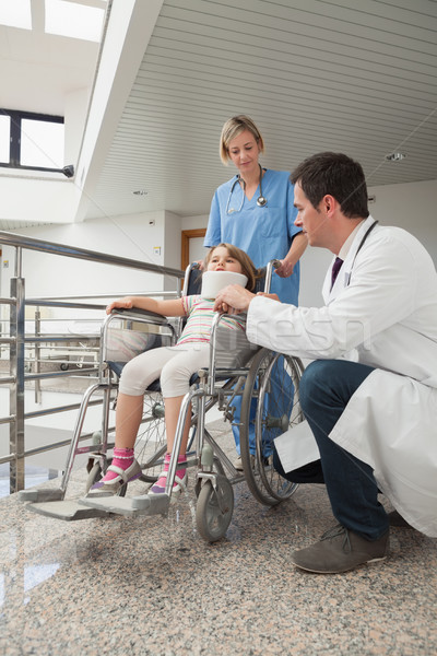 Doctor crouching next to child in wheelchair with neck brace with nurse pushing it Stock photo © wavebreak_media