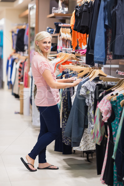 Woman is looking at clothes searching and smiling  Stock photo © wavebreak_media