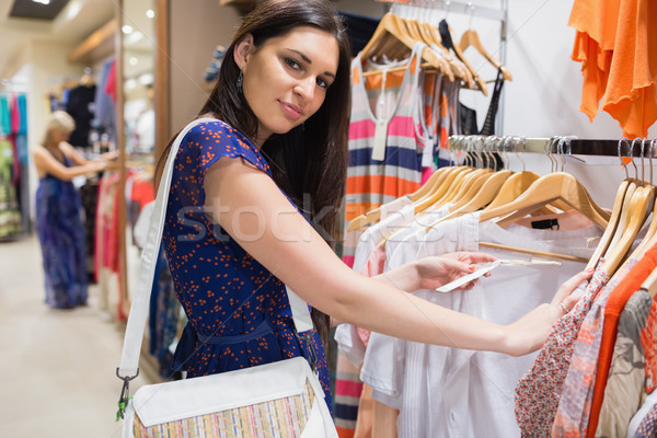 Woman with bag looking through clothes and smiling in shopping mall Stock photo © wavebreak_media