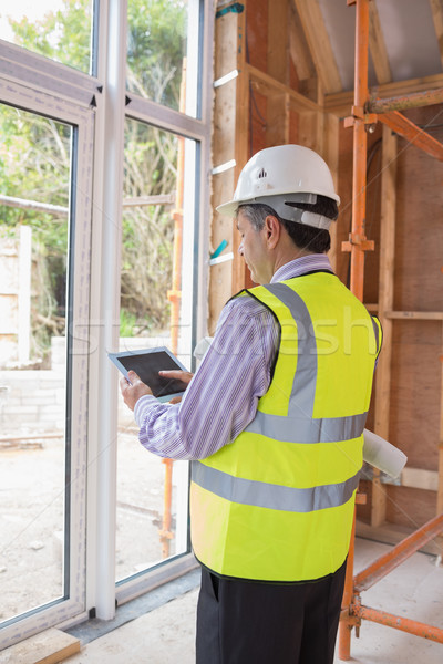 Man planning construction with the tablet pc while standing in the house Stock photo © wavebreak_media