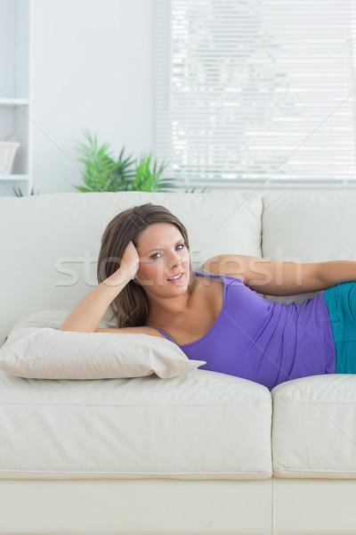 Calm brunette lying on sofa in the living room Stock photo © wavebreak_media
