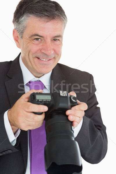 Smiling man in suit looking at pictures on digital camera Stock photo © wavebreak_media