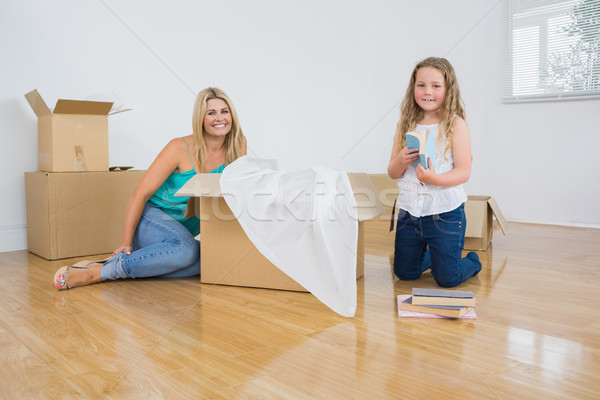 Smiling mother and daughter unpacking boxes Stock photo © wavebreak_media