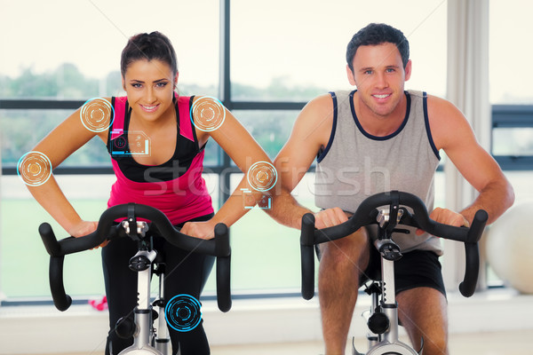 Composite image of young man and woman working out at spinning c Stock photo © wavebreak_media