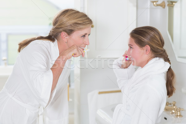 Happy mother and daughter brushing teeth together  Stock photo © wavebreak_media