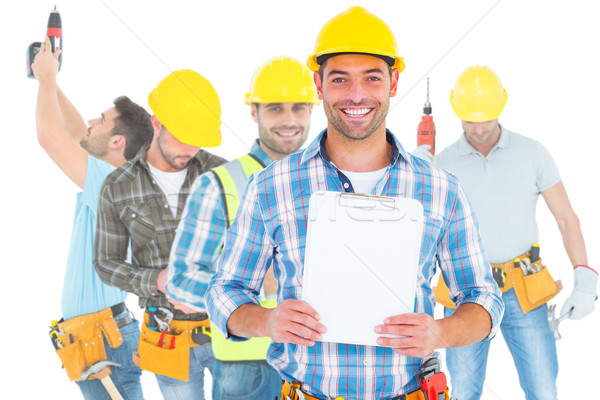 Stock photo: Composite image of portrait of smiling manual worker holding cli