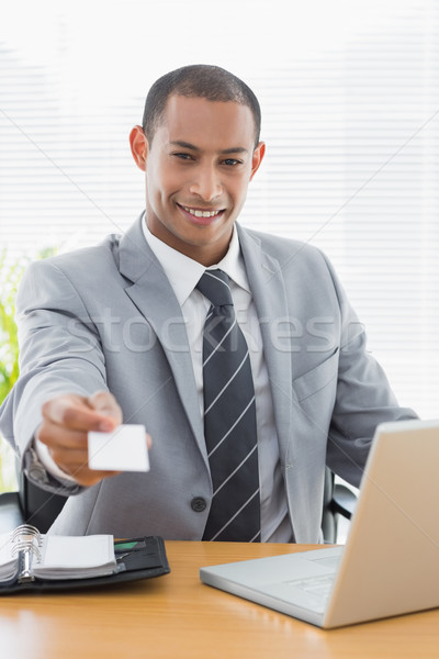 Well dressed man handing business card in front of laptop at off Stock photo © wavebreak_media