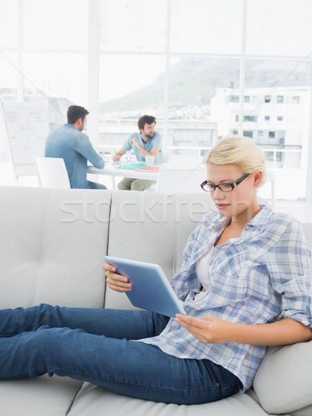 Woman using digital tablet with colleagues in background at crea Stock photo © wavebreak_media