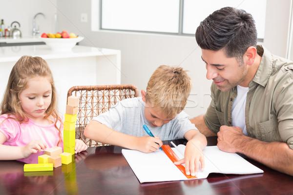 Padre ayudar hijo deberes nina jugando Foto stock © wavebreak_media
